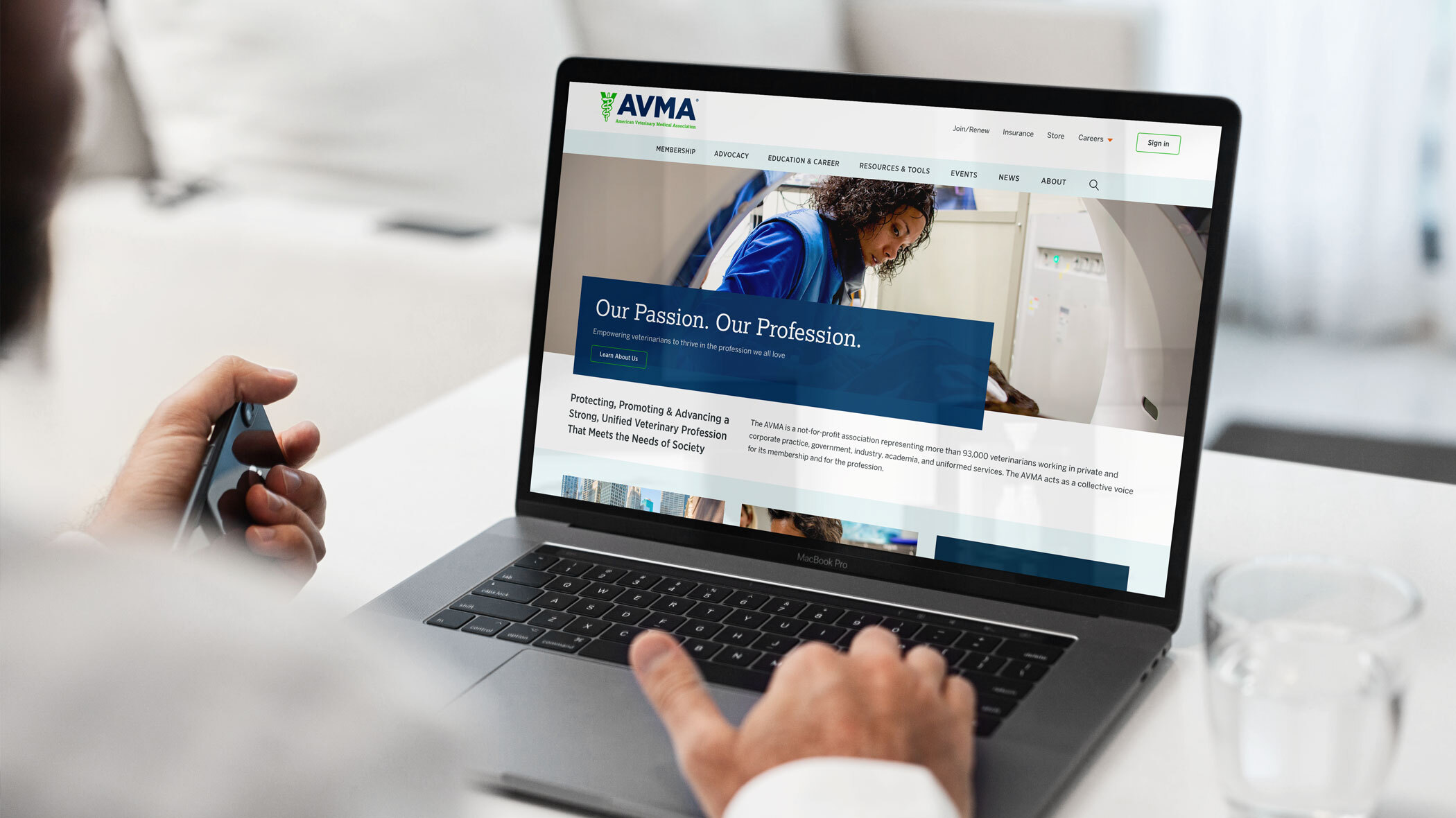 A doctor in a clinical setting viewing the AVMA website on a laptop